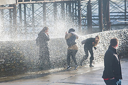 Brighton, UK. 21/11/2016, INDIA CONEY 17, BEZYA GEDIK 16 and YANA ROGER 16 get soaked as powerful waves are hitting the pontoon next to the Brighton Palace Pier. Photo Credit: Hugo Michiels