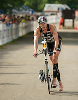 Pro athlete Andy Potts approaches the bike dismount at Ellacoya after completing the 55 mile course during Sunday's Ironman 70.3 Timberman Triathlon at Ellacoya State Beach.  (Karen Bobotas/for the Laconia Daily Sun)