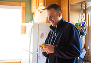 Nick Rhoades emails someone on his phone in his kitchen in Waterloo, Iowa on Thursday, November 7, 2013.