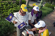 3 men are reading the 8 points policy program of the CNRP during a campaign rally led by Sam Rainsy in Kampong Cham, Cambodia.