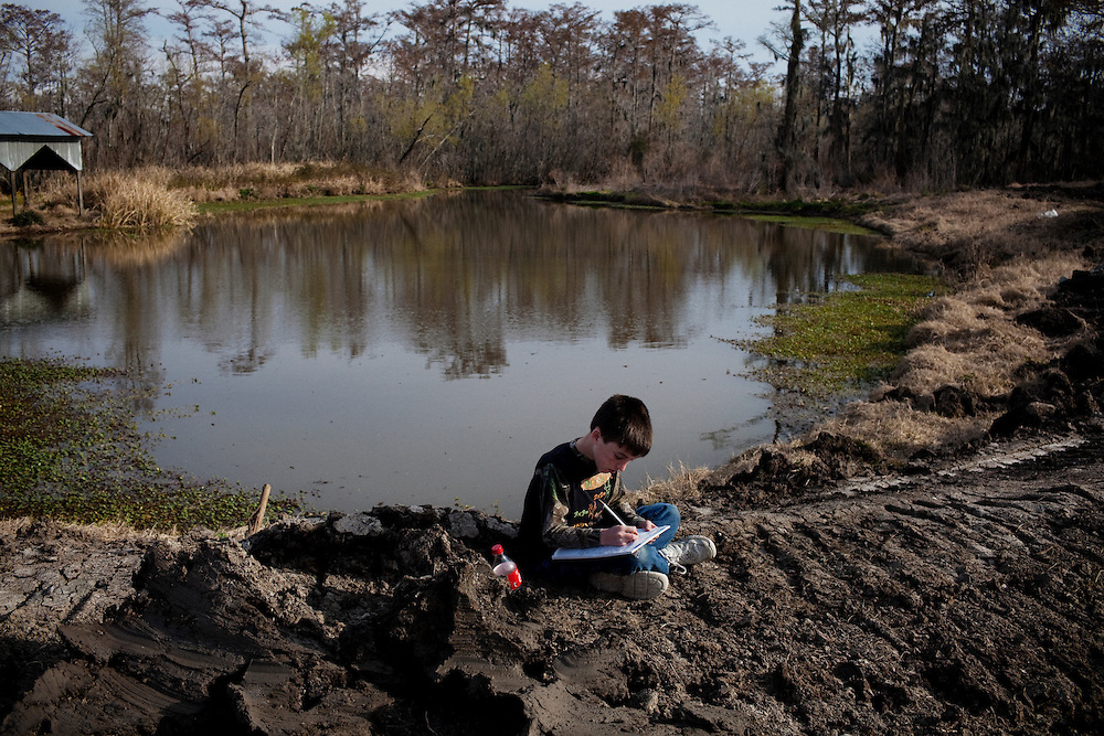 Stephen Paul Bonnecarrere, 10,  sits outside writing a paper for school by the pond at Daneco Alligator Farm in Houma, Louisiana on Friday, February 19, 2010.  The pond sits on the edge of their property and is hedged in by a swamp.
