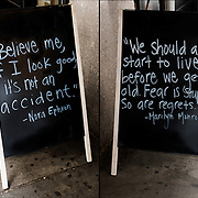 Blackboard quot on sign in front of Hair salon with quote from Nora Ephron and quote from Marilyn Monroe on the other side. <br />