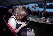 Cardiff University Ball in Cooper's Field, Cardiff, Wales, May 2000. Photograph © Rob Watkins. Pictured: A girl texting at an outside table