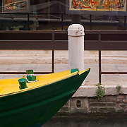 Wooden boat and art gallery window display on the Rio Pietre Blanche, Dorsoduro, Venice, Italy<br />