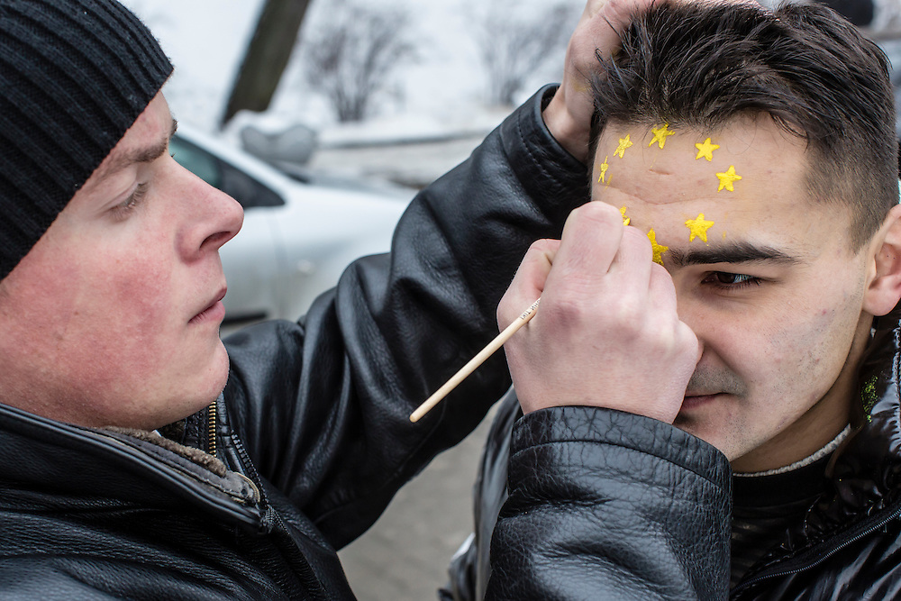 KIEV, UKRAINE - DECEMBER 12: A man has the stars of a European flag painted on his forehead by a friend during anti-government protests on December 12, 2013 in Kiev, Ukraine. Thousands of people have been protesting against the government since a decision by Ukrainian president Viktor Yanukovych to suspend a trade and partnership agreement with the European Union in favor of incentives from Russia. (Photo by Brendan Hoffman/Getty Images) *** Local Caption ***