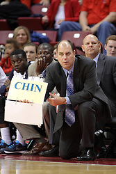 16 November 2014:  A coach from the Aggies holds a sign card with the current formation or play during an NCAA non-conference game between the Utah State Aggies and the Illinois State Redbirds.  The Aggies win the competition 60-55 at Redbird Arena in Normal Illinois.