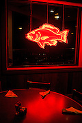 A neon fish illuminates the dining room at night at Angelo and Son's Seafood Restaurant in Panacea, Florida.