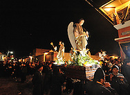 """During festive """"Semana Santa"""" (Saints week) in Antigua, Guatemala, day and night processions of people draped in robes, carry massive coffins with effigies of the crucified Jesus Christ. The floats weigh up to 7,000 pounds with 50-100 curcuruchas or carriers bearing their weight.  Funeral marching bands follow the floats, with slow beating drums, cymbals and deep-throated tubas. Thick incense creates a haunting, ghost-like fog. Crowds hush as the solemn procession passes by.  Antigua is a UNESCO World Heritage site."""