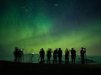 Photographers photographing the Northern Lights dancing over Jökulsárlón Glacial Lagoon, Southeast Iceland.