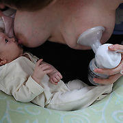 A two month old baby girl baby breast feeding as her mother uses a milk pump to express milk into a container on her other breast. Photo Tim Clayton
