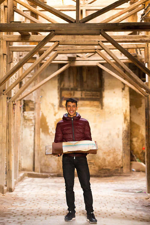 Portrait of local carrying a tray of freshly baked bread through the Fez Medina after using a communal oven, Fez Medina, Morocco, 2016-01-09.<br />