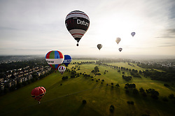 Balloons hover over long shadows of Clifton Downs as dozens of balloon pilots gather for a mass launch to mark less than a week to go until the start of the Bristol International Balloon Fiesta.