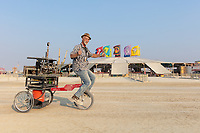 Shots Fired Espresso Cart by: PocoJoe and the Shots Fired Team from: Tucson, AZ year: 2018 (This fellow said can you take a photo of me so I can send it to my wife. She didn't think it was possible to put an espresso machine on a unicycle.) My Burning Man 2018 Photos:<br />