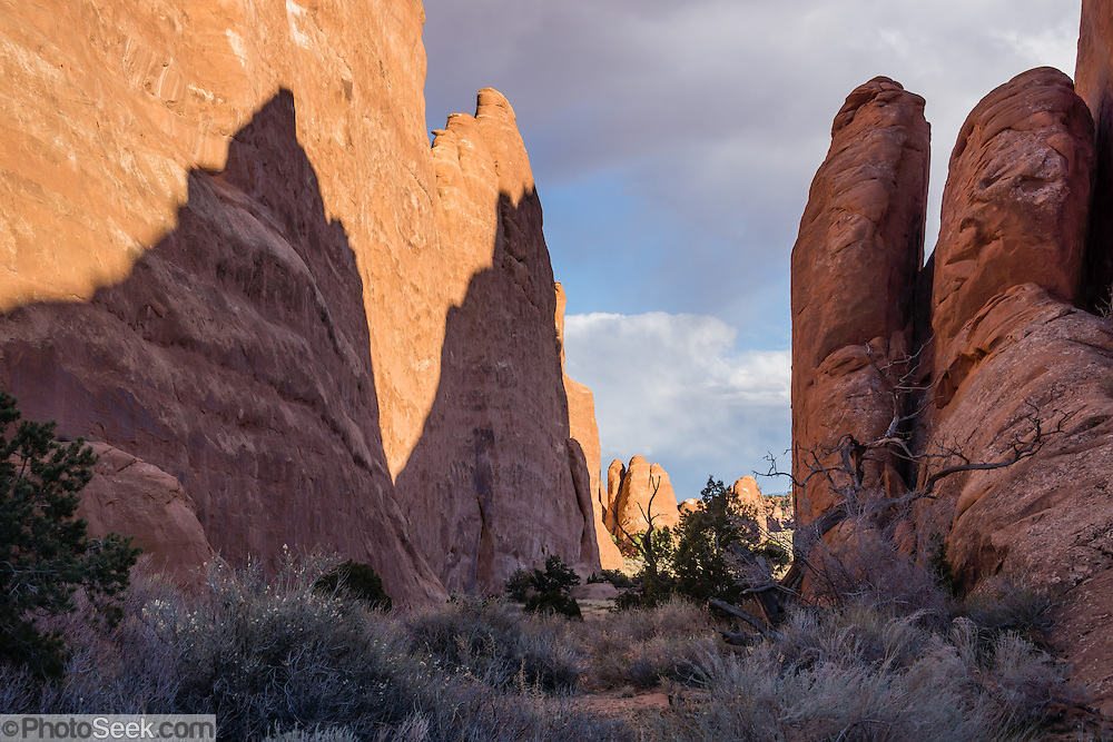 Red rock shadows, Arches National Park, near Moab, Utah, USA. A thick underground salt bed underlies the creation of the park's many arches, spires, balanced rocks, sandstone fins, and eroded monoliths. Some 300 million years ago, a sea flowed into the area and eventually evaporated to create the salt bed up to thousands of feet thick. Over millions of years, the salt bed was covered with debris eroded from the Uncompahgre Uplift to the northeast. During the Early Jurassic (about 210 million years ago) desert conditions deposited the vast Navajo Sandstone. On top of that, about 140 million years ago, the Entrada Sandstone was deposited from stream and windblown sediments. Later, over 5000 feet (1500 m) of younger sediments were deposited and then mostly worn away, leaving the park's arches eroded mostly within the Entrada formation.