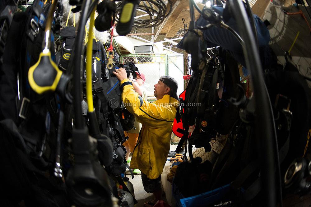 A man in a yellow jacket picks up dive gear in a dive locker. (Model Released)