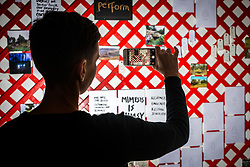 © Licensed to London News Pictures. 27/04/2018. Wakefield UK. A visitor takes a photograph on her phone of the latticework wall of photos & words by Alec Finlay at the Yorkshire Sculpture Park this morning. The art work features in a new exhibition at the park which showcases the radical & vital work of arts & environment charity Common Ground. Photo credit: Andrew McCaren/LNP