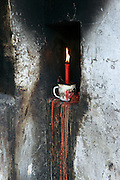 A red candle in a white cup burning, as it looks like it has for many years, in the courtyard of an ancient temple in Wenzhou, Zhejiang, China.