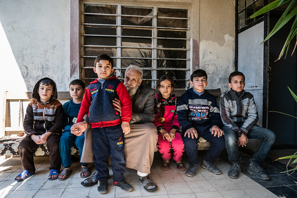 4 February 2019 – Mosul – Iraq – Father of seven Mishal Mohammed Hassan, 80, is pictured with his grandchildren outside their family home in West Mosul, which was occupied by ISIS and burned by the militants when they left. <br /> <br /> Mishal's home is now being rehabilitated with the support of UNDP's Funding Facility for Stabilization (FFS), which is supporting the rehabilitation of ten thousand homes across West Mosul, helping displaced families return home. <br /> <br /> © UNDP Iraq / Claire Thomas