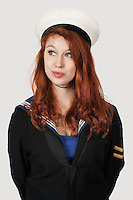 Thoughtful young woman in sailor's uniform looking away against gray background