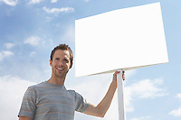 Man with standing by blank sign against cloudy sky