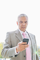 Businessman reading text message on cell phone against sky