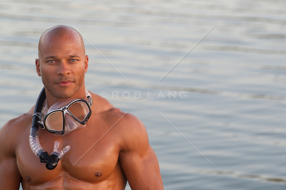 handsome African American muscular man without a shirt with a mask and snorkel around his neck at a lake