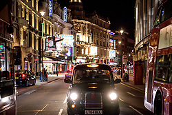 © Licensed to London News Pictures. 20/03/2020. London, UK. An empty black cab on Shaftesbury Avenue.  West End was left unprecedentedly empty on Friday night following the government's announcement that all bars, pubs and restaurants must be closed immediately in the latest step to curb the coronavirus outbreak.  Photo credit: Guilhem Baker/LNP