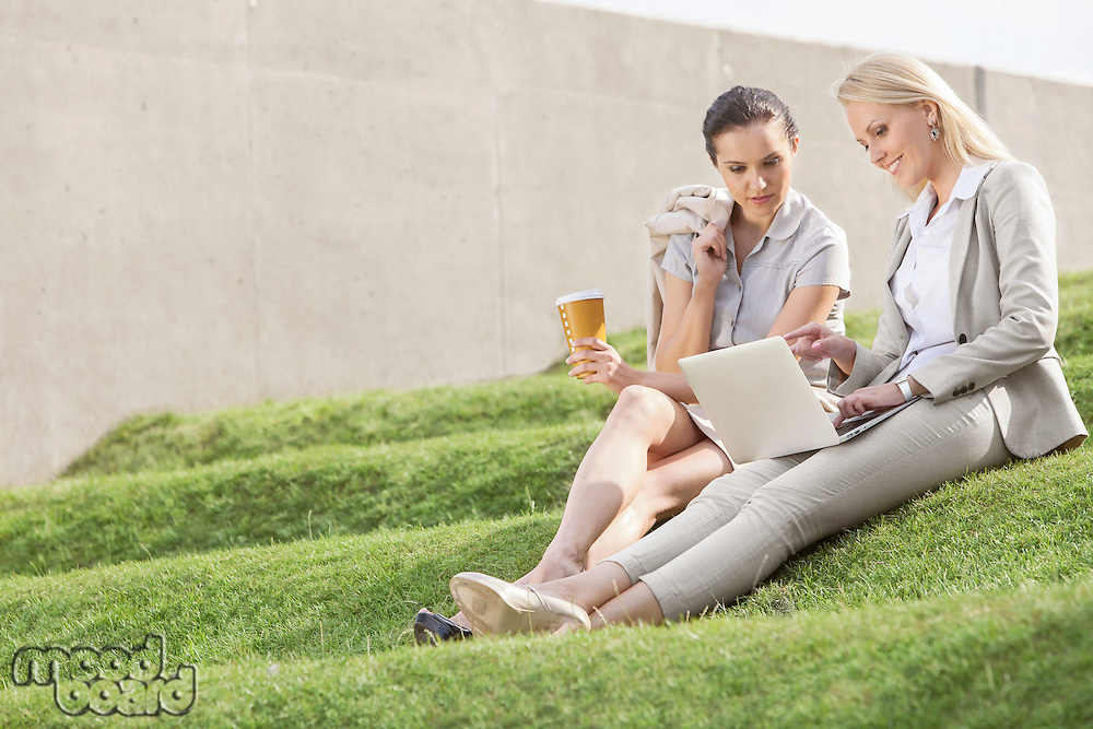 Full length of businesswomen with disposable coffee cup looking at laptop while sitting on grass steps