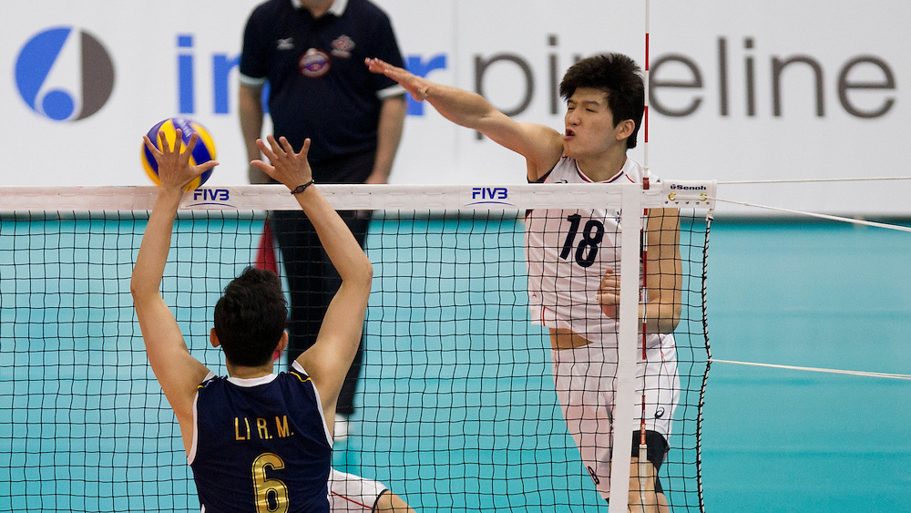 Jiseok Jung (18) of Korea spikes the ball on Runming Li of China at a World League Volleyball match at the Sasktel Centre in Saskatoon, Saskatchewan Canada on June 26, 2016.