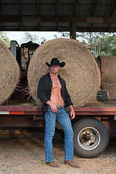 cowboy with an open shirt standing by hay bales on a truck