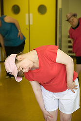 Day Service user with learning disability warming up before a dance class,