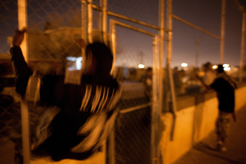 Members of the Noveno gang leave the closed soccer fields through a hole in the fence.