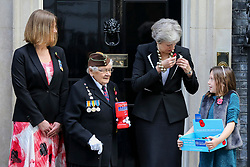 © Licensed to London News Pictures. 25/010/2018. London, UK. Prime Minister Theresa May pins a poppy to her jacket as she meets fundraisers Claire Rowcliffe, Director of Fundraising at The Royal British Legion, Barbara Windsor (93) and Poppy Railton (9) for the Royal British Legion and purchase a poppy to launch the National Poppy Appeal 2018 outside 10 Downing Street. Photo credit: Dinendra Haria/LNP