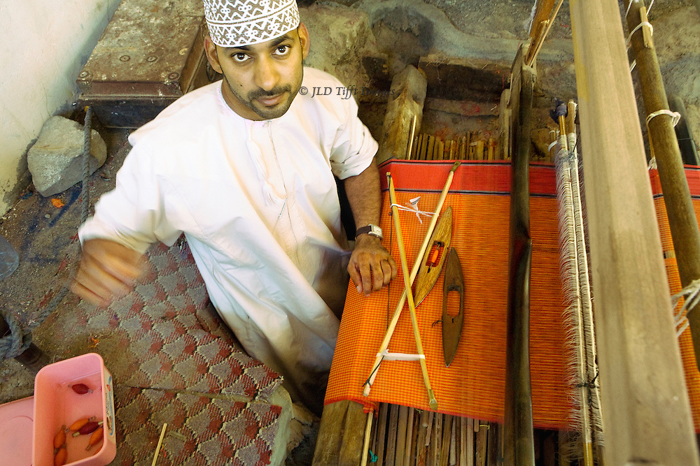 Oman, village of Samad, home of traditional pit weavers.  Weaver at work.