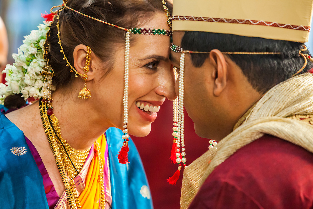 The happy bride and groom at an Indian wedding looking into one anothers eyes with their foreheads touching.