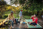 29 JUNE 2013 - BATTAMBANG, CAMBODIA:  Bamboo train drivers relax while they wait for passengers in O Sra Lav, a small village southeast of Battambang. The bamboo train, called a norry (nori) in Khmer is a 3m-long wood frame, covered lengthwise with slats made of ultra-light bamboo, that rests on two barbell-like bogies, the aft one connected by fan belts to a 6HP gasoline engine. The train runs on tracks originally laid by the French when Cambodia was a French colony. Years of war and neglect have made the tracks unsafe for regular trains.  Cambodians put 10 or 15 people on each one or up to three tonnes of rice and supplies. They cruise at about 15km/h. The Bamboo Train is very popular with tourists and now most of the trains around Battambang will only take tourists, who will pay a lot more than Cambodians can, to ride the train.       PHOTO BY JACK KURTZ