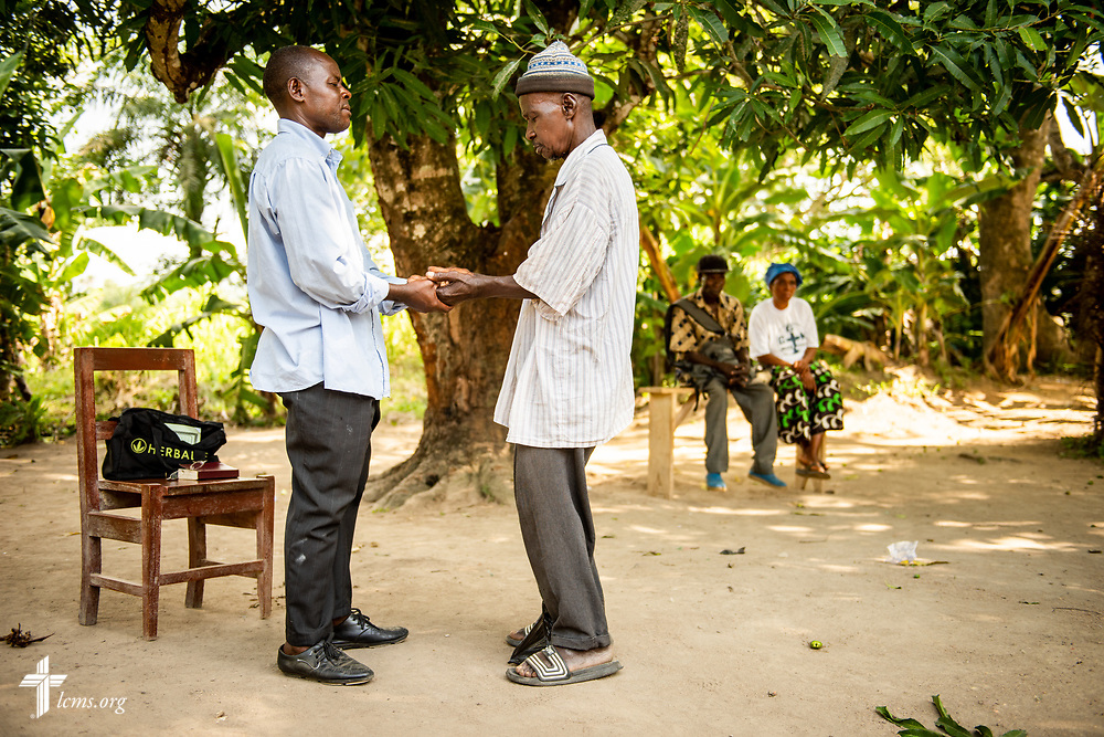 Pastor Nathaniel S. Abu of the Christ Evangelical Lutheran Church—Sierra Leone (CELC—SL), prays with a man following treatment on the first day of the LCMS Mercy Medical Team on Monday, May 7, 2018, in the Yardu village outside Koidu, Sierra Leone, West Africa. LCMS Communications/Erik M. Lunsford