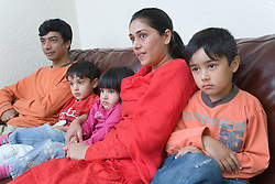 Young family sitting on the sofa watching television together,