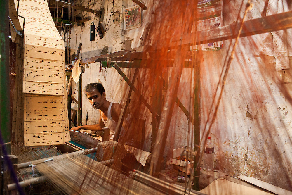 A worker operates the card punch loom that weaves traditional Jamdani sari in Mirpur Benarashi Palli, Dhaka, Bangladesh, a poor Bengali neighborhood.