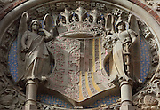Coat of arms of the Hospital de Santa Creu, with crown and angels, by Eusebi Arnau, 1864-1933, and Pau Gargallo, 1881-1934, above the main entrance of the Administration Pavilion, built 1905-10, at the Hospital de Sant Pau, or Hospital de la Santa Creu i Sant Pau, built 1902-30, designed by Catalan Modernist architect Lluis Domenech i Montaner, 1850-1923, in El Guinardo, Barcelona, Catalonia, Spain. The original medieval hospital of 1401 was replaced with this complex in the 20th century thanks to capital provided in the will of Pau Gil. The hospital consists of 27 pavilions surrounded by gardens and linked by tunnels, using the Modernist Art Nouveau style with great attention to detail. On the death of the architect, his son Pere Domenech i Roura took over the project. The complex was listed in 1997 as a UNESCO World Heritage Site. Picture by Manuel Cohen
