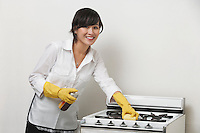 Portrait of young housemaid cleaning stove against gray background