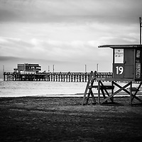 Newport Pier and lifeguard tower 19 on Balboa Peninsula in Newport Beach Southern California. Photo is black and white and high resolution.