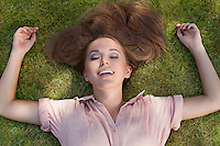 Relaxed young woman lying in grass at park
