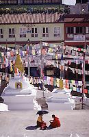 Two Buddhist nuns talk at the base of the Bodnath Stupa, Kathmandu Valley, Nepal