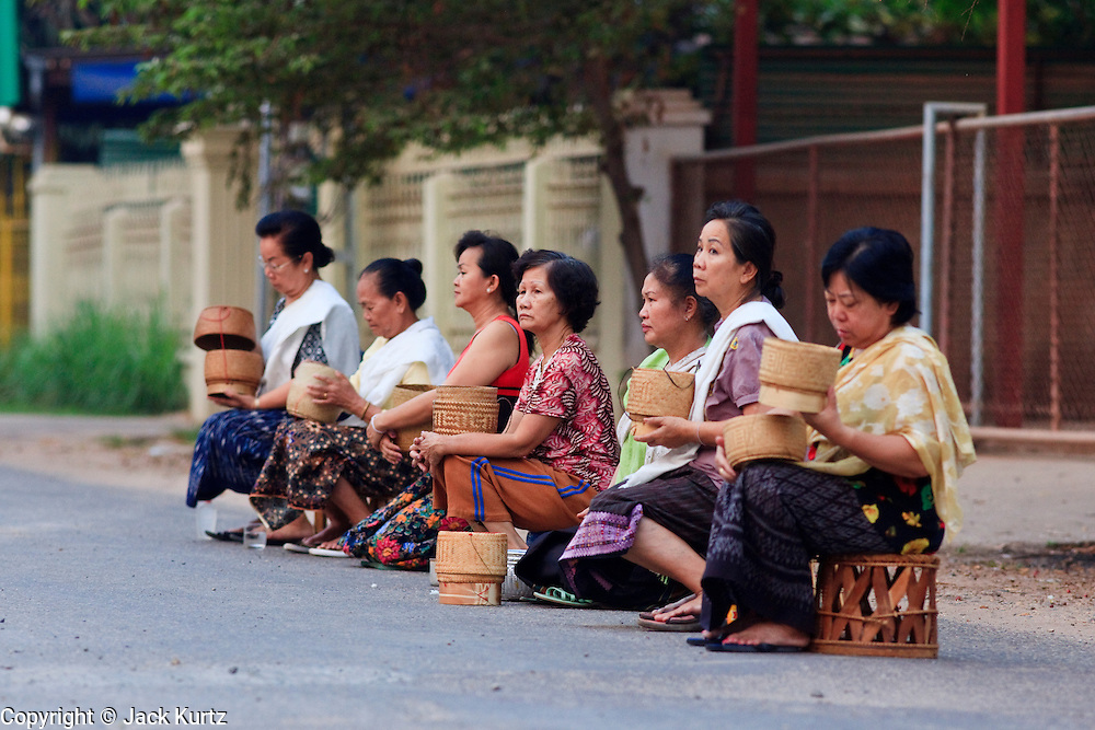 "12 MARCH 2009 -- VIENTIANE, LAOS:  Women wait to give rice to Buddhist Monks in Vientiane, Laos, who go about their ""Tak Bat,"" Lao for ""monks morning rounds."" The monks collect alms in the form of food from people who line their route. For the monks, it is the only food they get that day, for the people it's a chance to ""make merit."" Photo By Jack Kurtz"