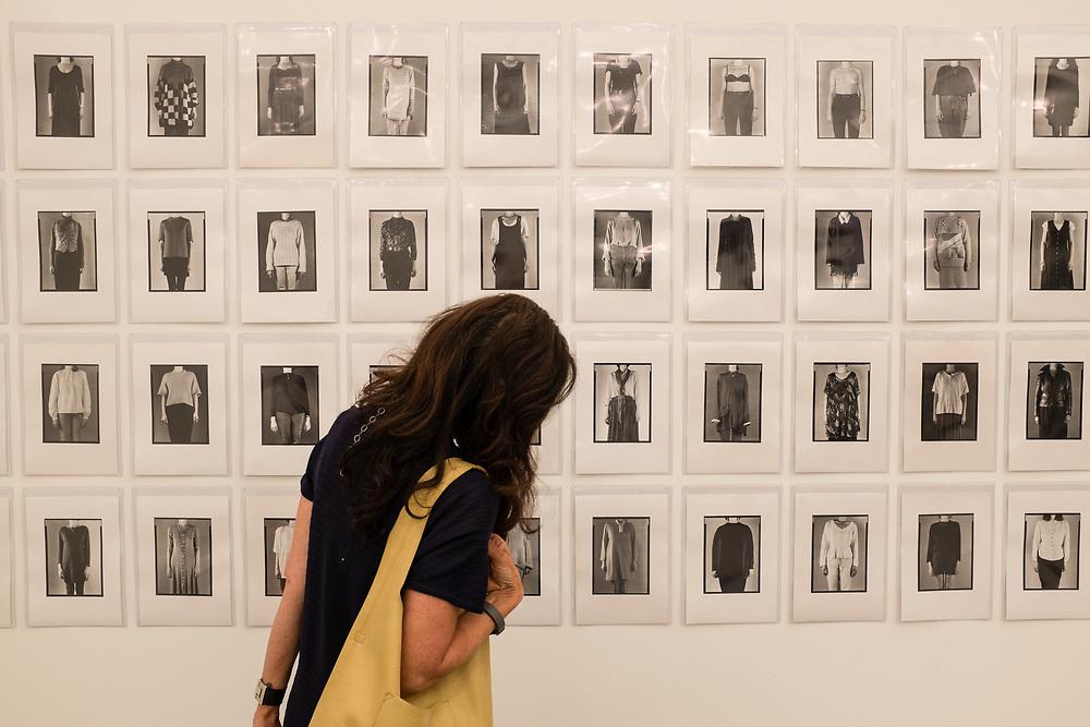 New York, NY - May 3, 2019.  woman looking at Gintautas Tramakas' photographs at the PM8 Gallery at the Frieze Art Fair on New York City's Randalls Island.