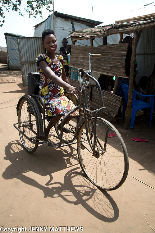 Uganda . Adjumani. Flora Limio  in Ayilo refugee camp settlement near Pakelle. She is a hairdresser and has a physical disability. She uses an adapted bicycle.