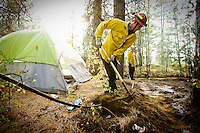 JEROME A. POLLOS/Press ..Coeur d'Alene firefighter Jeff Canfield digs through the soil at a transient camp to extinguish hot spots after a fire Sept. 25 near Northwest Blvd.
