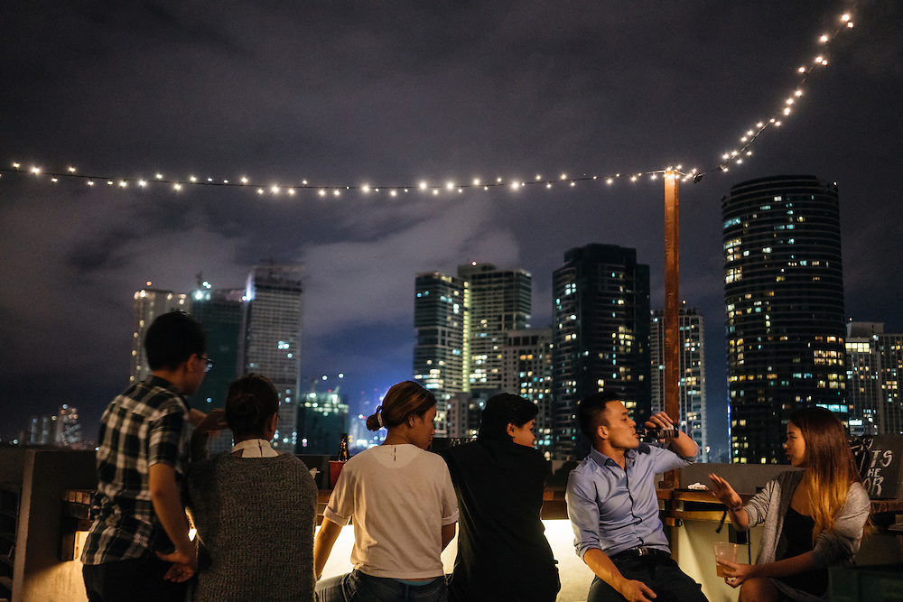 "Vincent Lau of Oakland, Ca. meets his friend Angeline Manahan, from Manila, at the rooftop bar at Z Hostel, with the Rockwell city skyline in the distance in Manila, Philippines. ""The Philippines is definitely under the radar."" Lau, who is launching a health care company in Manila, said."