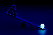Several black balls are outweighed by a single glowing white ball on a see saw.Black light